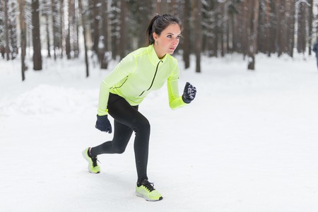 cross street with care: Fit woman in position ready to run outdoors winter park.