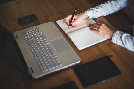 persona escribiendo: freelancer mujer de manos de una mujer con lápiz de escribir en el cuaderno en el hogar o la oficina