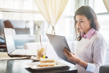 girl with laptop: Businesswoman in a restaurant reading a contract document