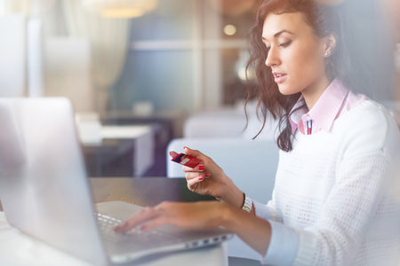 Young businesswoman drinking coffee and using laptop computer in cafe doing online shopping, holding credit card