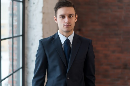 graduation suit: Portrait of a confident young businessman standing in office Stock Photo