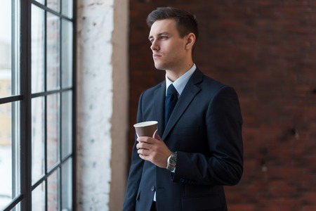 rich life: Businessman drinking coffee in office standing near window