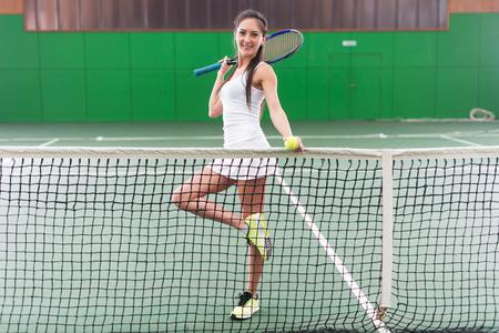 jugando tenis: Retrato de cuerpo entero de una mujer joven jugando al tenis en una cancha