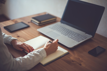 teleworker: Woman freelancer female hands with pen writing on notebook at home or office