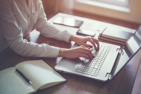 Mujer que trabaja en la oficina en casa mano en el teclado de cerca.