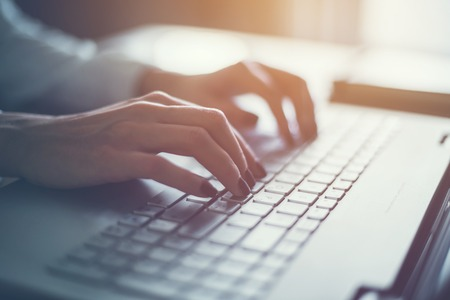 coder: Working at home with laptop woman writing a blog. Female hands on the keyboard. Stock Photo