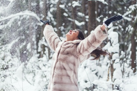 woman playing with snow in fur coat outdoors winter park Stock Photo
