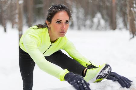 deportistas: Invierno Preparación física modelo de atleta chica caliente se extiende su isquiotibiales, las piernas y la espalda