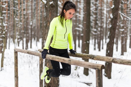 jungle gyms: Fit woman exercising outdoors doing triceps dips on parallel bars at park. Street workout winter.