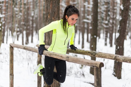 triceps: Fit woman doing triceps dips on parallel bars in woods