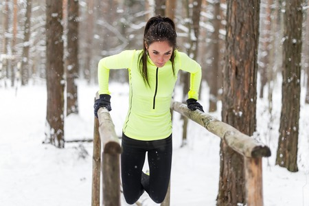 outdoor fitness: Fit woman exercising outdoors doing triceps dips on parallel bars at park. Street workout winter.