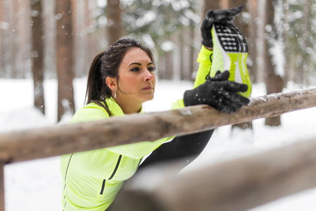 Fit woman athlete doing left leg split stretching exercises outdoors in woods. Female sports model exercising outdoor winter park. Stock Photo