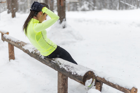 situp: Fit woman doing sit ups working out on abdominal muscles exercising to improve core muscle strength cross training outdoors winter park