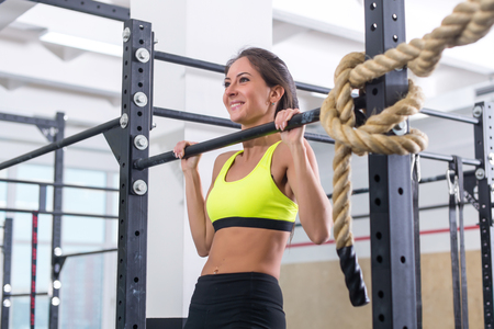 cross bar: Fitness woman pull ups on horizontal bar in gym
