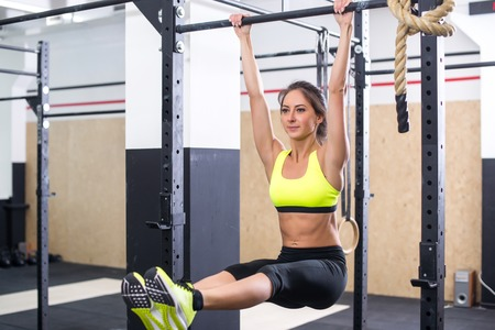 cross bar: Fit girl training abs by raising legs on a horisontal bar. Fitness woman workout doing exercises at gym