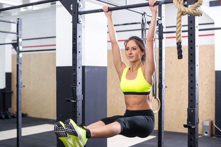 cuerpo femenino: La muchacha del ajuste de formación abs, elevando las piernas en una barra de horisontal. Mujer entrenamiento de la aptitud que hace ejercicios en la gimnasia
