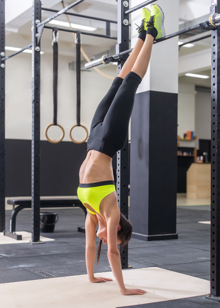 dorsi: Fit woman doing handstand Athlete standing on hands Concept balance sport fitness