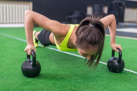 push ups: Fit woman young doing push ups exercise with dumbbells in the gym.