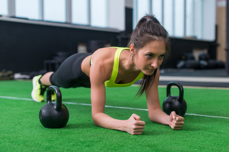 forearm: Fit woman doing plank exercise working on abdominal muscles in the gym.