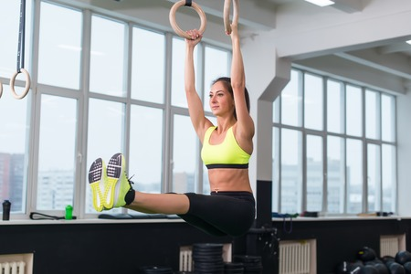 to raise: Fit woman exercising with gymnastic rings raising legs in gym Stock Photo