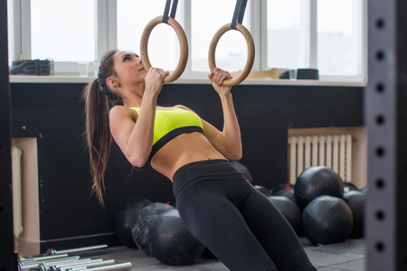 pullups: Fit woman going pull-ups with gymnastic rings in gym.