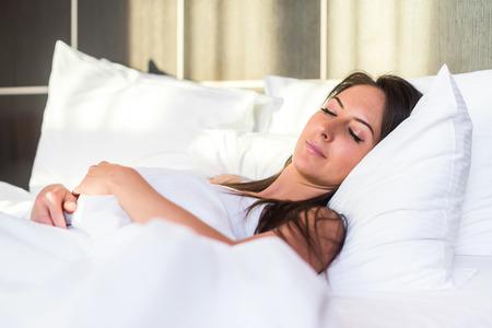 wellness sleepy: Beautiful girl sleeps at the bedroom lying in bed.