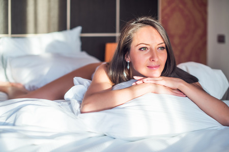 relaxing at home: Beautiful smiling woman lying in her bedroom