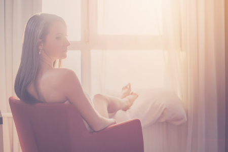 admiring: Lovely woman sitting and looking through a window admiring sunrise or sunset