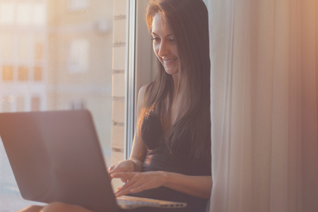 girl with laptop: Woman smiling and using laptop computer at home sitting near window.