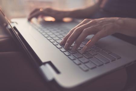 ホーム オフィスの手をキーボードで作業ノート パソコンで入力女性 写真素材