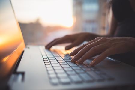Mujer que trabaja en la oficina en casa la mano en el teclado de cerca.