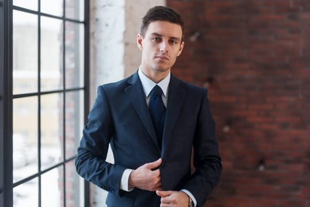 office man: Young serious man standing near office window. Manager director boss entrepreneur employer Stock Photo