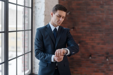 authenticity: Businessman standing near office window looking on his wrist watch