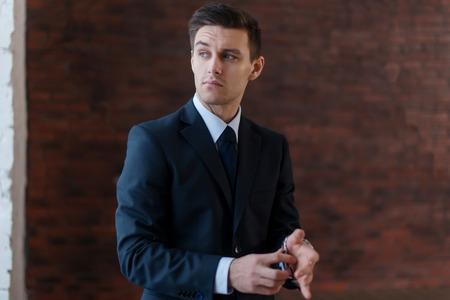 retardation: Businessman wearing wrist watch standing near office window looking away. Stock Photo
