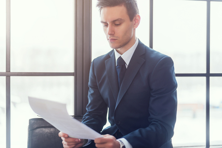 is real: Businessman sitting in office reading contract documents. Stock Photo