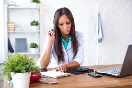 white coat: Portrait of physician doctor working in medical office workplace writing prescription sitting at desk Stock Photo
