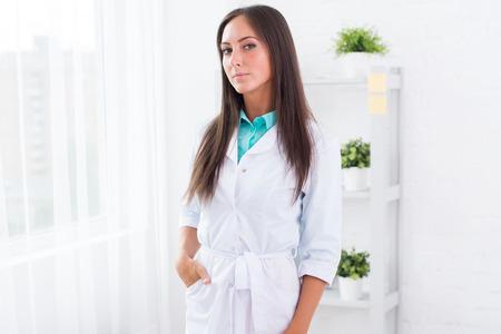 bata blanca: Retrato de mujer joven m�dico con bata blanca que se coloca en el consultorio m�dico mirando a la c�mara