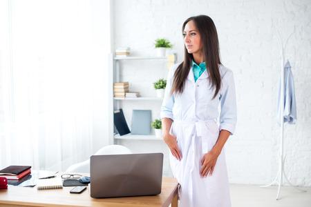 bata blanca: Retrato de mujer joven m�dico con bata blanca que se coloca en el consultorio m�dico. Foto de archivo