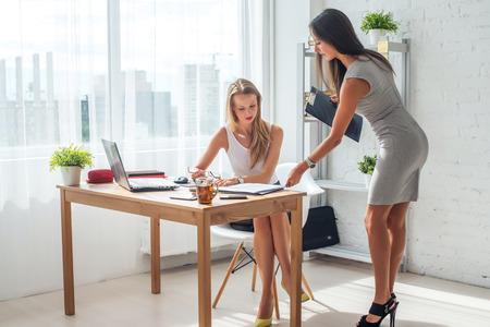 Deux jeunes femme travaillant ensemble dans le bureau. Subordonnés et patron