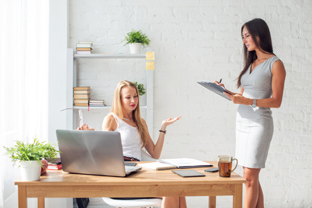 woman in office: Two young woman colleague at office working and talking.