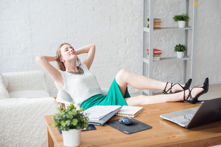 lazy: Businesswoman resting relaxing legs on the table hands behind her head and sitting on a chair in office