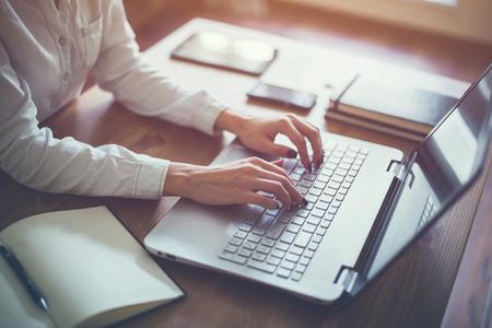 Fêmea que trabalha com portátil em mãos da mulher em casa no caderno computador Escritor desenhador blogger teletrabalho Imagens - 55682678