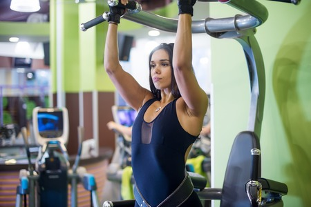 strong chin: Woman performing pull ups in a bar at gym Stock Photo