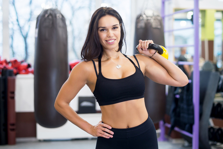 Fitness woman doing shoulder press swing exercise with a kettlebell lifting heavy weight smilling and looking at camera.