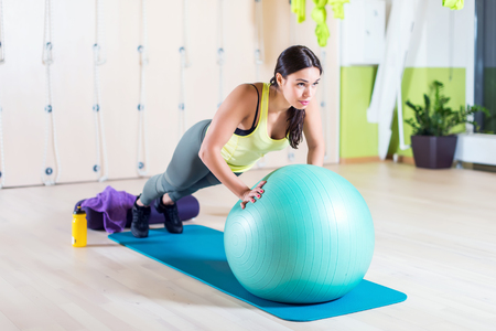 pectorals: Fit woman doing push ups with medicine ball workout out arms Exercise training triceps and pectorals muscles.