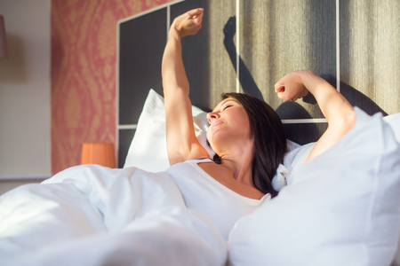 young woman waking up stretching in bed at home.