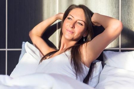 woman stretching: young woman full of energy, waking up, smilling, stretching in bed.