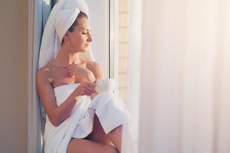 mujer bañandose: hermosa mujer sentada junto a la ventana, disfrutando de la salida del sol después de la ducha.