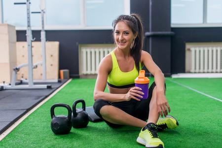 joven mujer deportivo agua potable en el gimnasio, sosteniendo la botella, que tiene descanso.