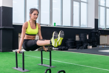 cross bar: fit strong woman doing L-sits work-out in gym, lifting up her legs, using parallel bars. Stock Photo